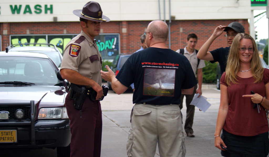 Ron Gravelle (sporting a T-shirt with his famous Colorado tornado published in National Geographic) talks to a state trooper after one of our vehicles is rear ended on the highway. Jenna Stevens points out the state trooper's dashing good looks. (Photo by Kirsten Koza)