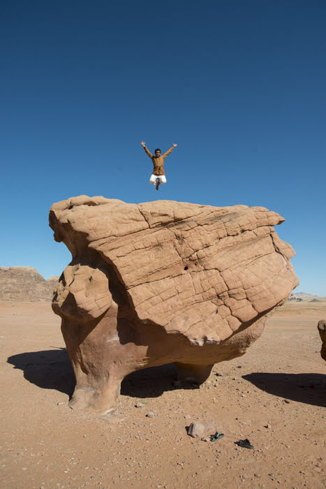 One of our Bedouin hosts leaps on this natural Wadi Rum rock formation. (Photo by Christopher Campbell, Writers' Expeditions)