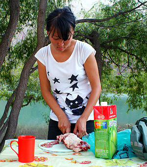 Kyrgyzstan, Cholpon chops chicken at Lake Ak-Kol  (Photo by Kirsten Koza)